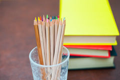 Colored pencils with pile of books in background Stock Photos