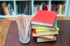 Colored pencils with pile of books with colored covers Royalty Free Stock Photos