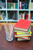 Colored pencils with pile of books with colored covers Royalty Free Stock Images