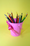 Colored pencils in pink pail Royalty Free Stock Image