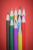 Colored pencils on red background Stock Images