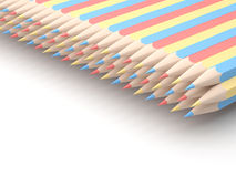 Colored pencils of red blue and yellow arranged in pattern on wh Royalty Free Stock Image