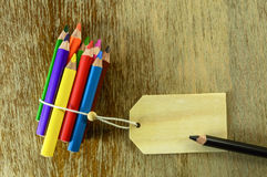 Colored pencils with room for text. Colored multiple pencils bound toghether opposing one black pencil with room for text Stock Photos