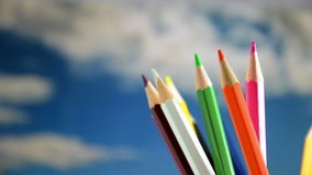 Colored pencils, rotation in the background the sky. Stock Photos