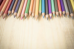 Colored pencils in a row on wood background Royalty Free Stock Photography