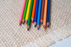 Colored pencils on sacking. Background Stock Photos