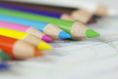 Colored pencils and scribbles. Line of colored pencils with scribbled paper Royalty Free Stock Images