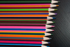 Colored pencils set on black wood background, Stock Photography