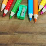 Colored pencils and sharpener on wooden background Stock Photography