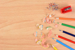 Colored Pencils and Shavings. High angle view of six colored pencils on a school desk with a sharpener and shavings. Horizontal with copy space. Back to school Royalty Free Stock Image