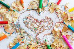 Colored pencils and shavings from pencils, drawing heart. The concept of love to art and drawing Royalty Free Stock Photo