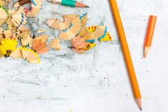 Colored pencils and shavings. On textured background with scratches Royalty Free Stock Photography