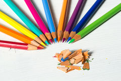 Colored pencils and shavings on white wooden table Royalty Free Stock Images