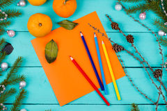 Colored pencils, sheet of paper and tangerines. On a wooden table Stock Image