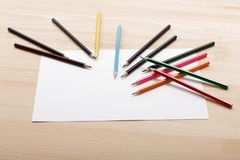 colored pencils and sheet of white paper on desk Stock Photo