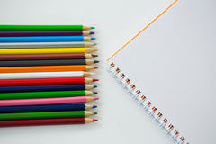 Colored pencils with spiral book. On white background Stock Images