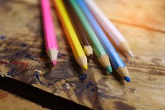 Colored pencils in a stand on a wooden table. School of drawing, children`s creativity stock illustration