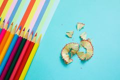 Colored pencils, trash and rainbow colorful stripes royalty free stock image