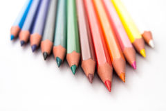 Colored Pencils in Triangle Formation. Multicolored pencils in a white background in a triangle formation. The red one is in front and focused. Others are royalty free stock photos