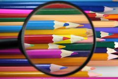 Colored pencils under loop - careful choice of color Royalty Free Stock Photos