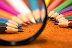 Colored pencils under the magnifying glass Royalty Free Stock Photo