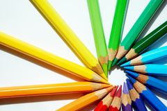Colored pencils of various colors are making a circle against their heads. Various sharpened pencils are making their heads against each other and making a stock photo