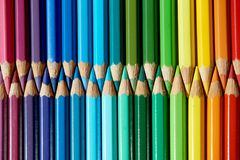 Colored pencils of various colors are placed face to face. The colored pencils of various colors are staggered with their heads facing each other stock photo