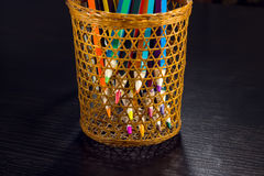 Colored pencils are visible through a wicker glass Stock Image