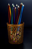 Colored pencils are visible through a wicker glass Stock Photo