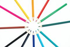 Colored pencils on white background. Rainbow in a circle royalty free stock photo