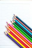 Colored pencils on white background. Set of colored pencils isolated on the notebook. Close up, left to right, top view Royalty Free Stock Image
