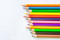 Colored pencils on white background. Set of colored pencils isolated on the notebook. Close up, left to right, top view Royalty Free Stock Photo