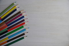 Colored pencils on white background. Colored pencils on white wooden background Royalty Free Stock Photo