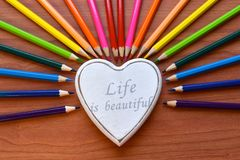 Colored pencils and white heart on the brown wooden table background Stock Photos