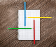 Colored pencils on white notebook Stock Photos