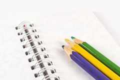 Colored pencils on white notebook. Office supplies on white background Royalty Free Stock Image