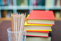 Colored Pencils With Pile Of Books In Background Stock Photo