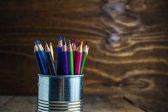 Colored pencils on wood. Colored pencils stuck in a can on old wood Royalty Free Stock Photos