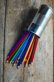 Colored pencils on wood. Colored pencils stuck in a can on old wood Royalty Free Stock Photo