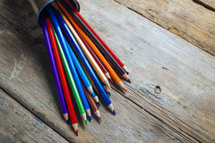 Colored pencils on wood. Colored pencils stuck in a can on old wood Stock Image