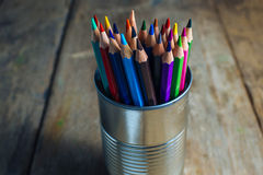 Colored pencils on wood. Colored pencils stuck in a can on old wood Royalty Free Stock Image