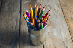 Colored pencils on wood. Colored pencils stuck in a can on old wood Royalty Free Stock Photography