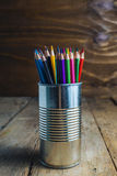 Colored pencils on wood. Colored pencils stuck in a can on old wood Royalty Free Stock Images