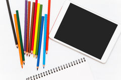 Colored pencils on wood table. Blank notebook and tablet. Wiew from above. Mockup royalty free stock image