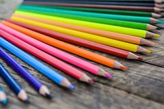 Colored pencils on wooden background Royalty Free Stock Photos
