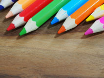 Colored pencils on wooden background Royalty Free Stock Images