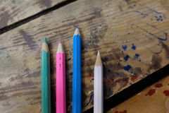 Colored pencils are on a wooden table. School of drawing, children`s creativity stock photos