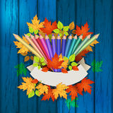 Colored pencils on a wooden texture with autumn leaves Stock Image