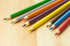 Colored pencils on wooden texture Royalty Free Stock Image