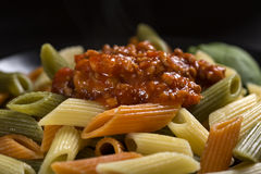 Colored penne pasta with ragu sauce or bolognese pasta. On plate Stock Photo